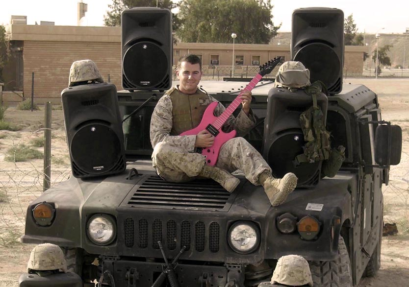 Military Student Andrew Bonica, wearing camo, on a Jeep, with a pink guitar